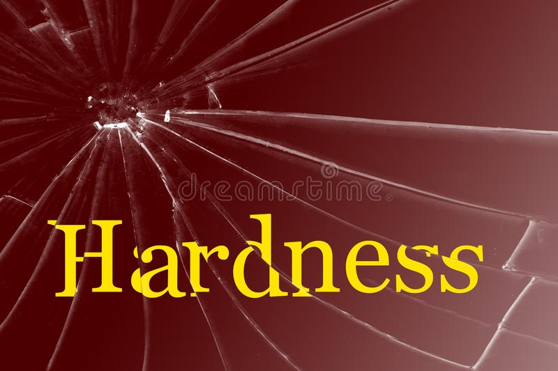 The text Hardness on the broken glass. Background stock photo