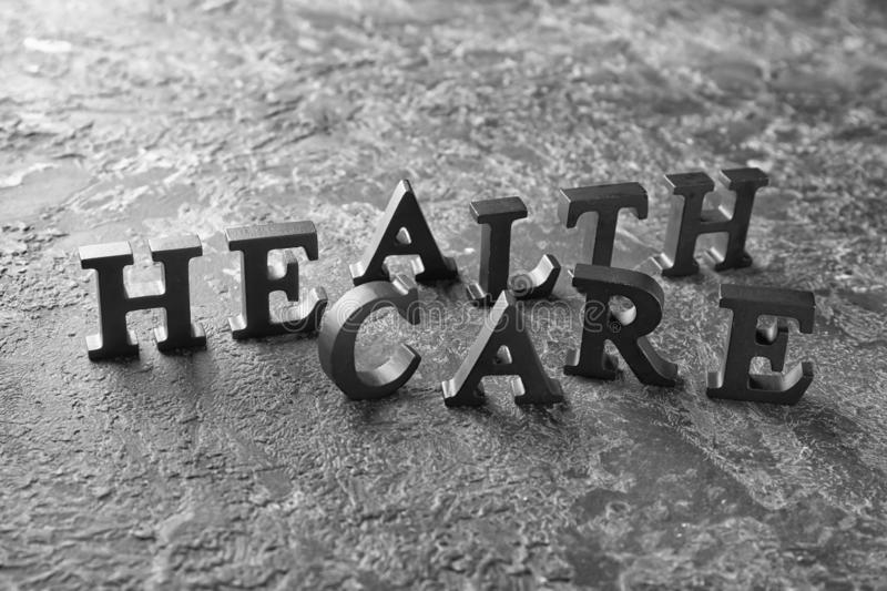 Text HEALTH CARE made of dark letters on grey table stock photography