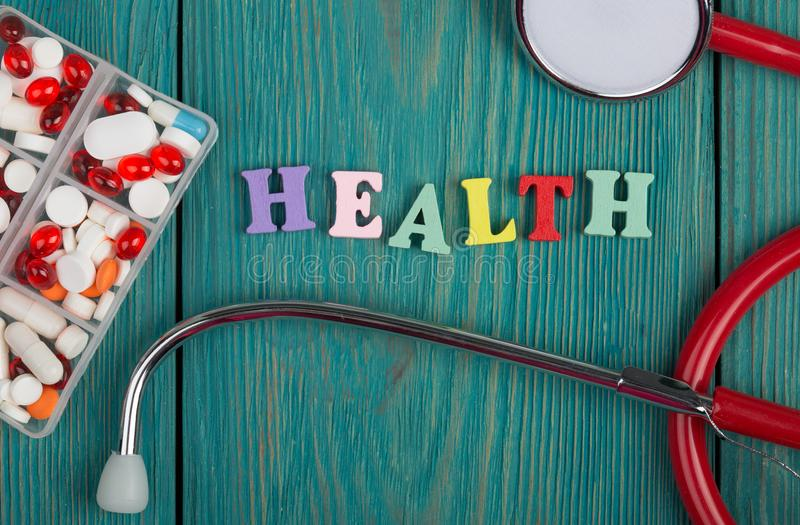 Text & x22;Health& x22; of colored wooden letters, stethoscope and pills. On a blue wooden background stock image