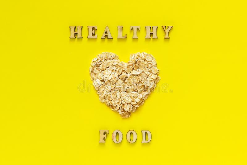 Text Healthy Food and oatmeal oat flakes in the shape heart on yellow background. Text Healthy Food and oatmeal oat flakes in shape heart on yellow background royalty free stock images