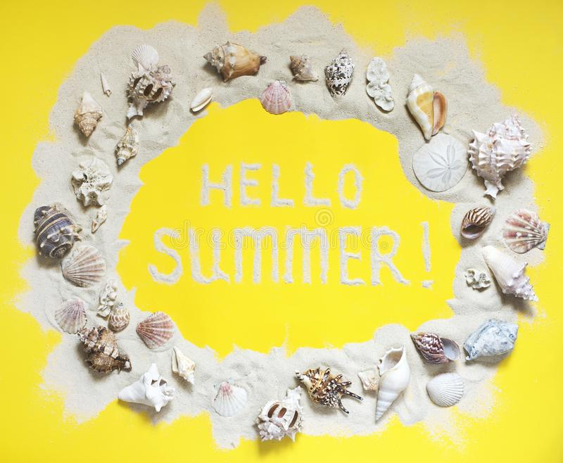 Text Hello Summer, exotic seashells and starfish collection flat lay on a yellow background. Top view royalty free stock photography