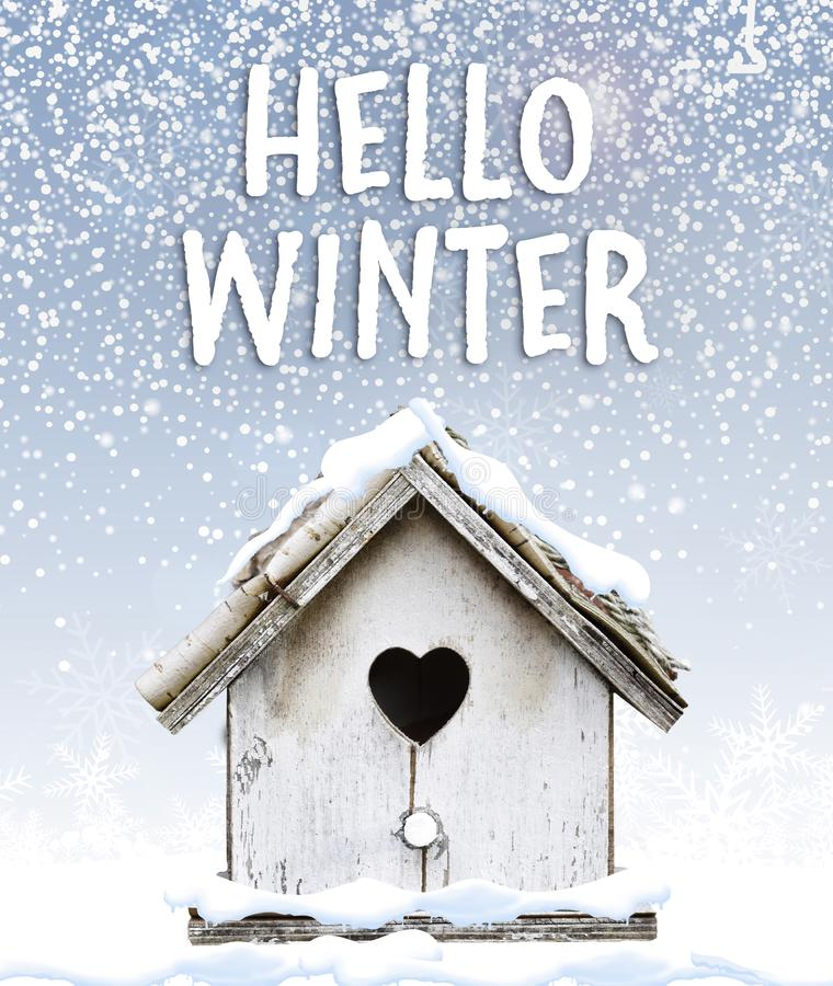Text hello winter with cute little bird house under snow quote stock images