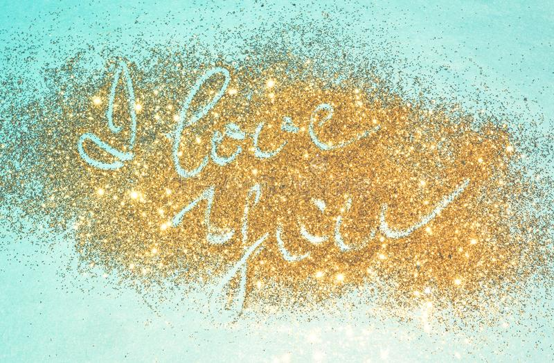Text I Love You of golden glitter sparkles on blue background royalty free stock photography