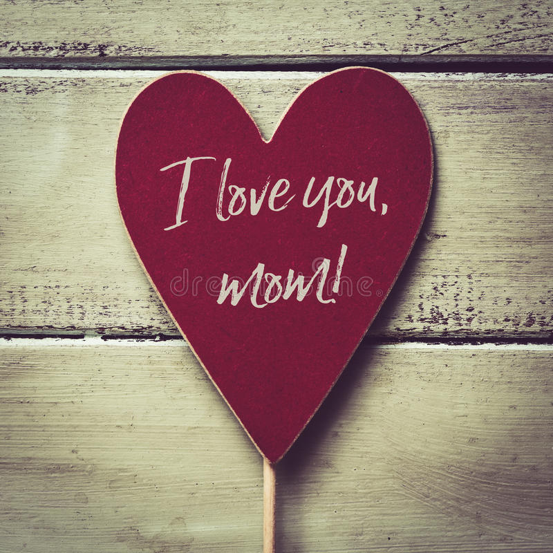 Text I love you mom. Closeup of a red heart-shaped signboard with the text I love you mom written in it, against a pale green rustic wooden background stock image