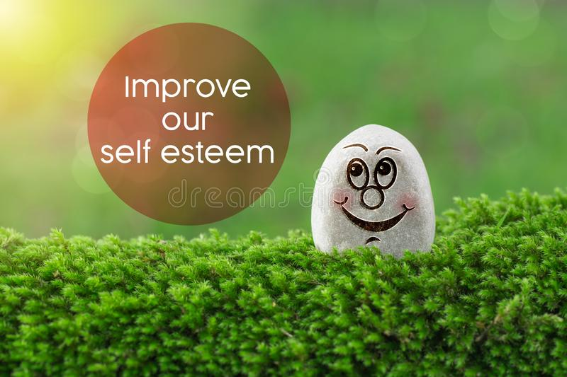 Improve our self esteem. The text Improve our self esteem with stone smile happy face on green moss and sunshine light background stock photography