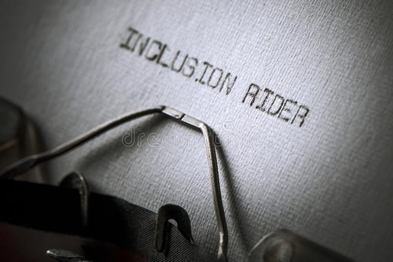 Text inclusion rider written with a typewriter. Closeup of an old typewriter and the text inclusion rider typewritten with it in a paper, with a slight vignette stock image