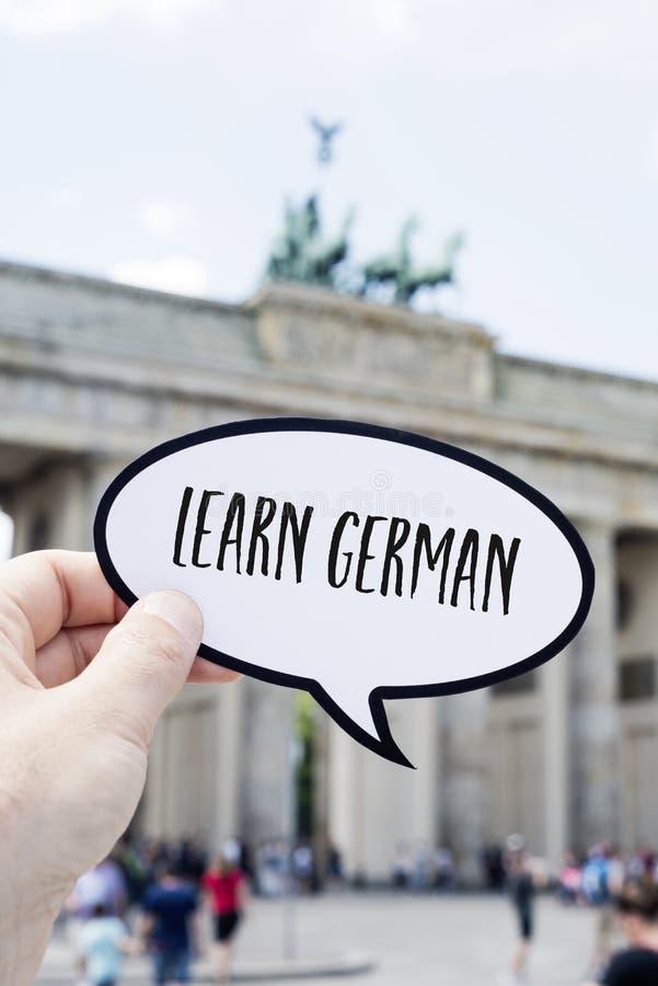 Text lär tysk framme av den Brandenburg porten arkivbild