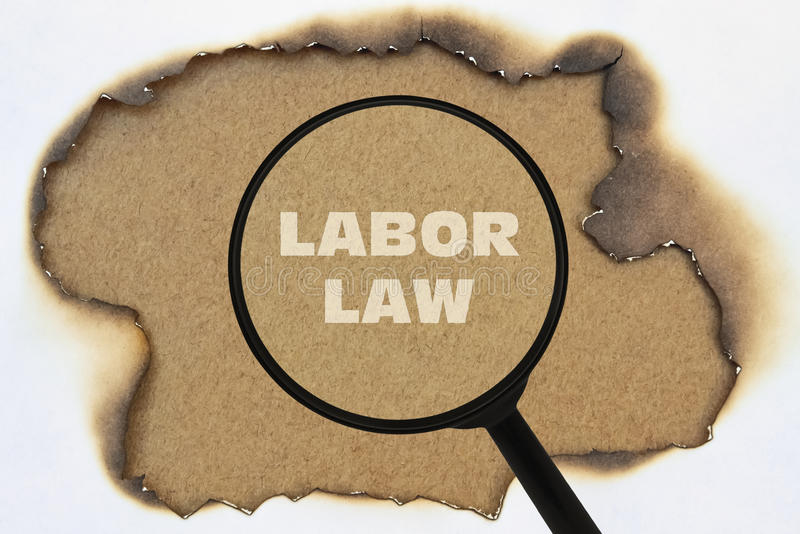 Text Labor Law. Written under a magnifier on a burnt paper royalty free stock images