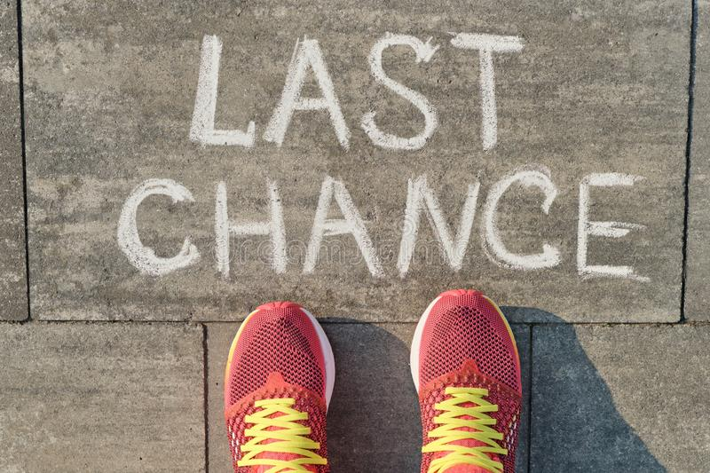Text last chance written on gray sidewalk with women legs in sneakers, top view.  stock images