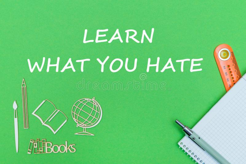 Text learn what you hate, school supplies wooden miniatures, notebook on green background. Concept school, text learn what you hate, school supplies, notebook royalty free stock photography