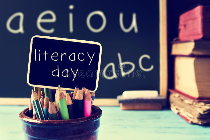 Text literacy day in a chalkboard, in a classroom, filtered. The text literacy day written in a chalkboard, in a retro and rustic classroom, with a filter effect royalty free stock image