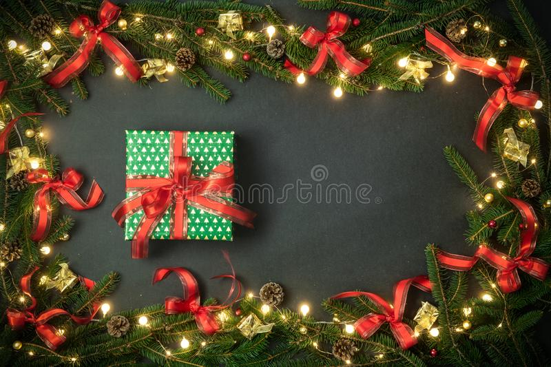 Text or logo empty copy space in vertical top view dark blackboard with pine branches,ribbons, lights decorated frame stock photos