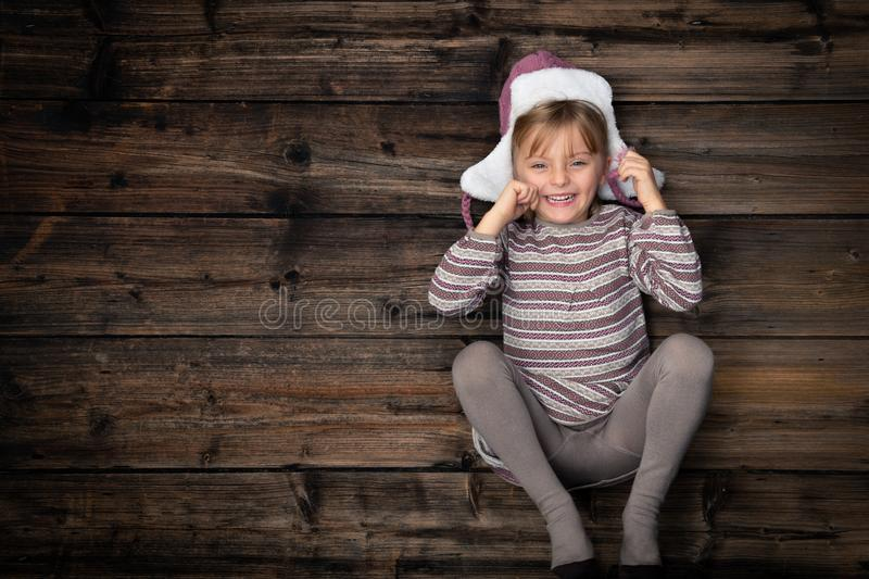 Text or logo empty copy space in vertical top view dark vintage wood.Beautiful happy child girl in homewear.Childhood stock images