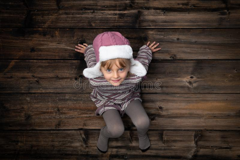 Text or logo empty copy space in vertical top view dark vintage wood.Beautiful happy smiling child girl in homewear stock photography