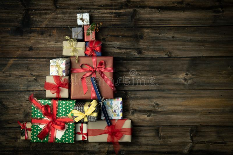 Text or logo empty copy space in vertical top view dark vintage wood with christmas tree pine made of gift present boxes stock photo