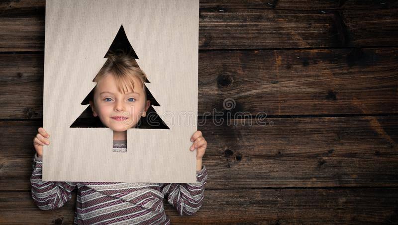 Text or logo empty copy space,vertical top view dark vintage wood.Happy child girl in homewear with cardboard tree pine stock images