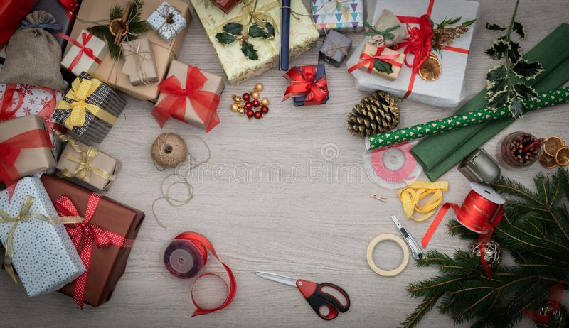 Text or logo empty copy space in vertical top view wooden table full of christmas gifts presents, pine and handicraft royalty free stock photo