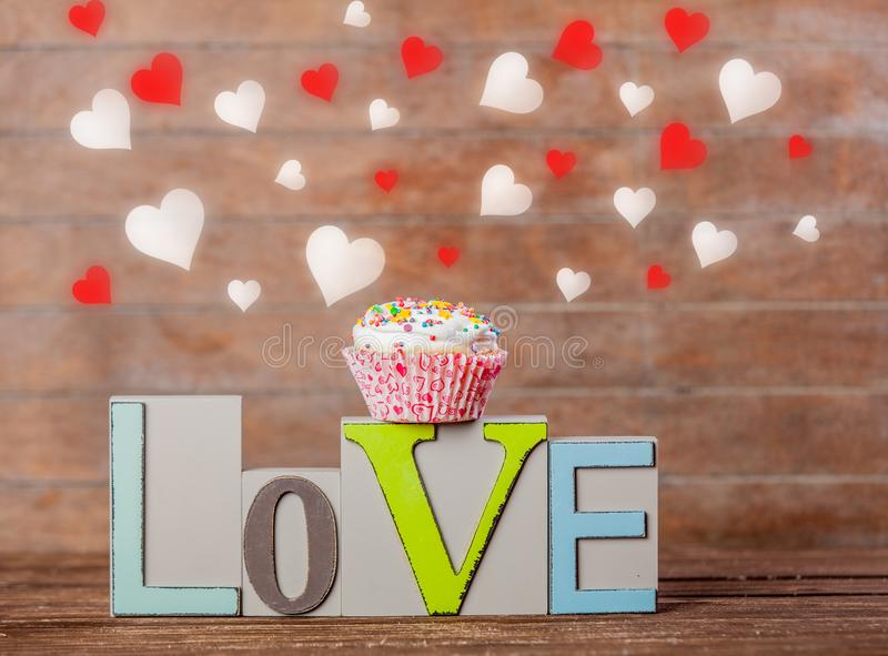 Text love and cupcake with heart shapes royalty free stock photography