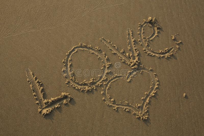 Love written in the sand and a heart drawn in the sand stock image