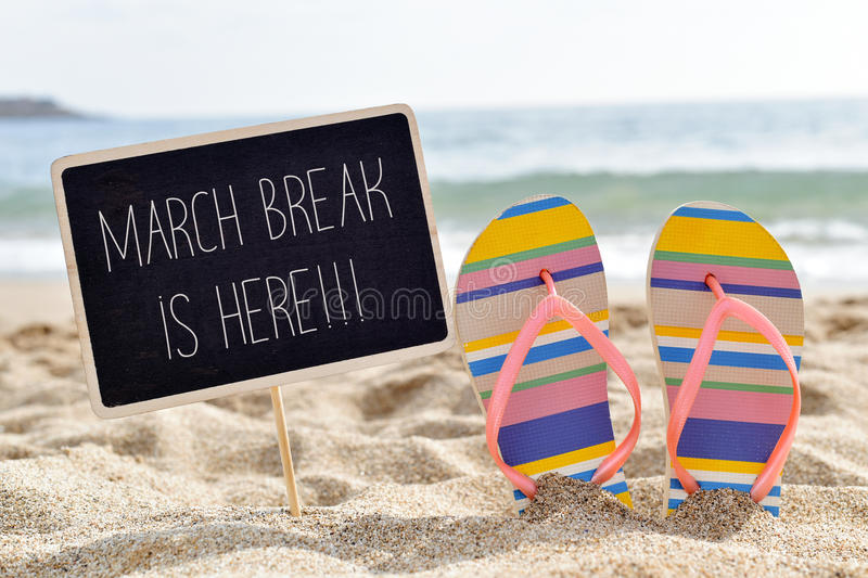 Text march break is here on the beach. Closeup of a chalkboard with the text march break is here written in it and a pair of flip-flops on the sand of a lonely royalty free stock images