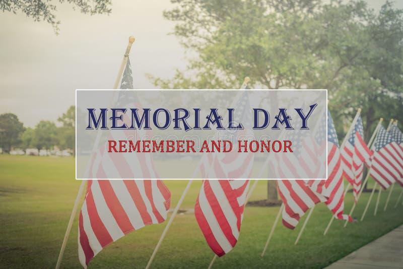 Text Memorial Day e a honra na fileira de bandeiras americanas do gramado foto de stock