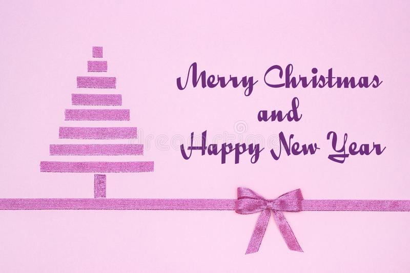 Merry Christmas and Happy New Year. Text Merry Christmas and Happy New Year. Abstract christmas tree from decorative shiny ribbon with bow on pastel paper pink royalty free stock images