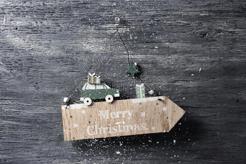 Text merry christmas in a wooden signboard. A homemade arrow-shaped wooden signboard with the text merry christmas written in, pinned in a gray rustic wooden stock images