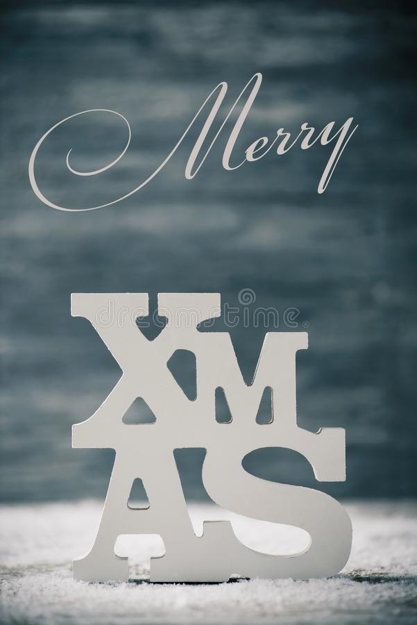 Text merry xmas. The word merry and the three-dimensional word xmas, forming the sentence merry christmas, against a rustic background on surface covered of stock photo