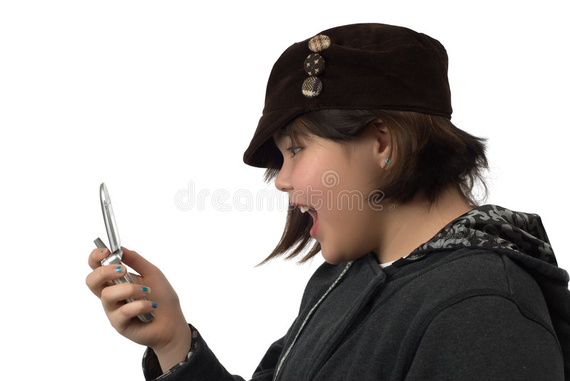 Text Message Kid. A young girl reading a text message on a cell phone, isolated against a white background royalty free stock photography