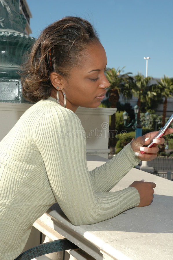 Text Messaging. Beautiful Black woman standing outside in a city scene using her cell phone. Woman with expressions on her face as she uses her cell phone. Text stock photos