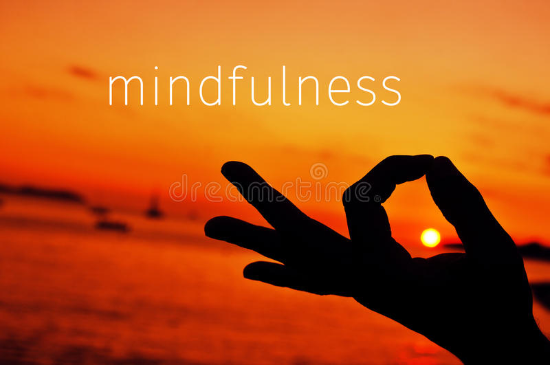 Text mindfulness and hand in gyan mudra at sunset. The text mindfulness and a closeup of a young man meditating with his hand in gyan mudra at sunset stock photo