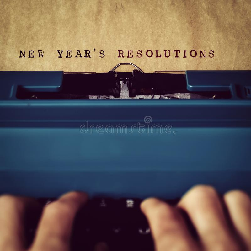 Text new years resolutions written with typewriter. Closeup of a man typewriting the text new years resolutions in a yellowish paper with a blue retro typewriter stock photography
