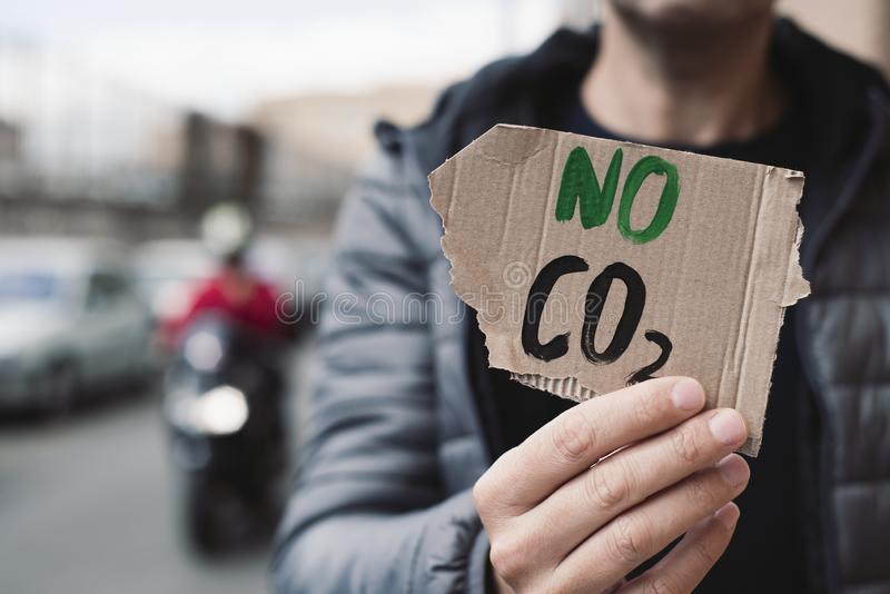 Text no CO2 in a cardboard signboard. Closeup of a young caucasian man, on the street, showing a brown cardboard signboard with the text no CO2 handwritten in it royalty free stock photography