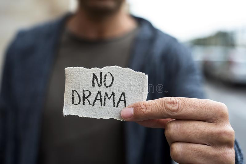Text no drama in a piece of paper. Closeup of a young caucasian man on the street, wearing casual clothes, showing a piece of paper with the text no drama stock photos