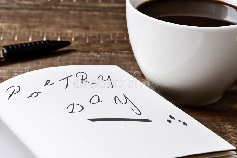 Text o dia da poesia em um caderno e em uma xícara de café fotografia de stock royalty free