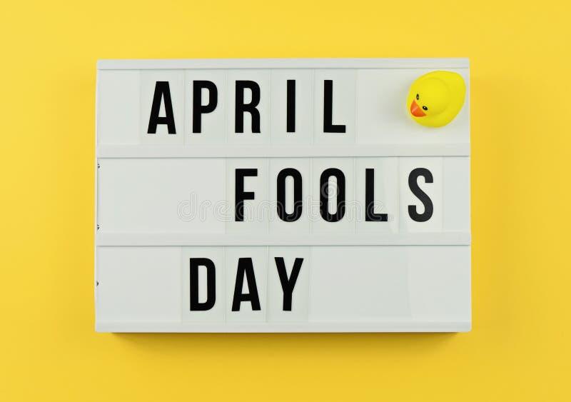Text o dia do ` s de April Fool na caixa leve no amarelo fotografia de stock