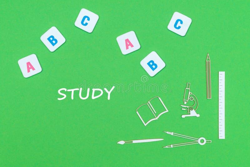 Text o estudo, de cima das fontes de escola de madeira dos minitures e das letras do ABC no fundo verde fotografia de stock