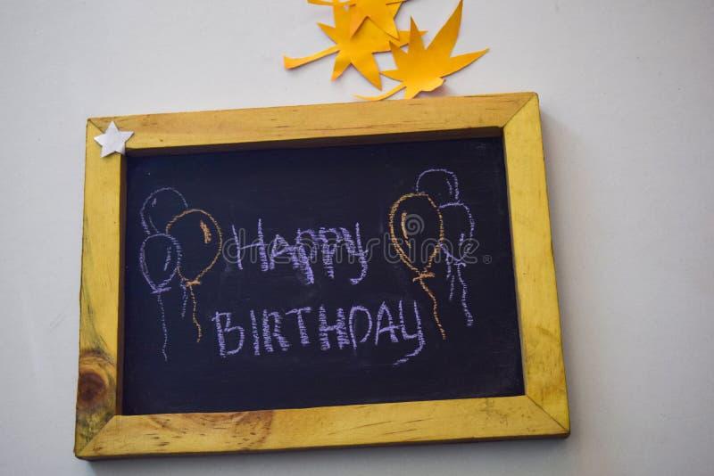 Text o feliz aniversario no quadro e no giz colorido, origâmi da folha do outono Fundo branco fotografia de stock