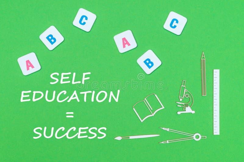 Text o sucesso da educação do auto, de cima das fontes de escola de madeira dos minitures e das letras do ABC no fundo verde imagem de stock