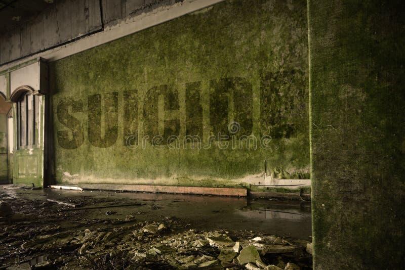 Text o suicídio na parede suja em uma casa arruinada abandonada fotografia de stock