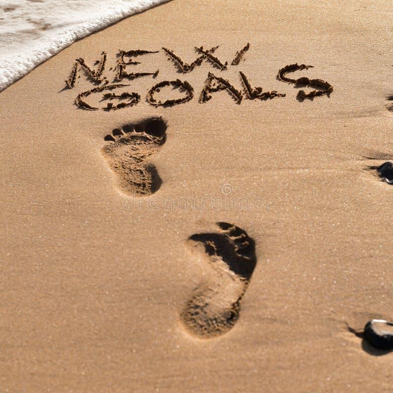 Text objetivos novos na areia de uma praia imagens de stock
