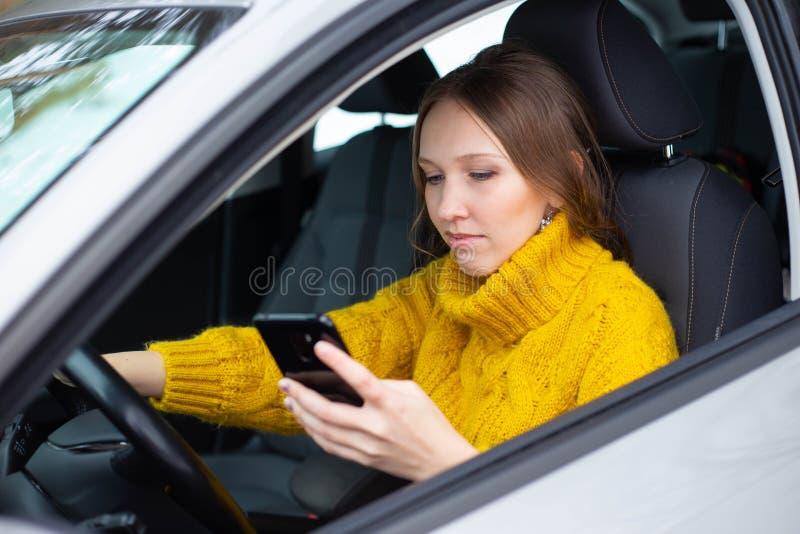 Text och drevkvinna En kvinna smsar p? hennes telefon, medan k?ra fotografering för bildbyråer