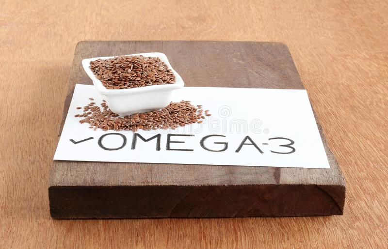 Text `Omega-3` Handwritten on a Paper and Flax Seed stock image