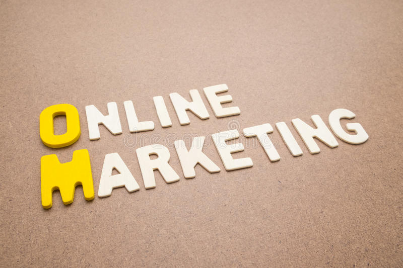 Text Online Marketing wording on brown background. Text 'Online Marketing' wording on brown background - Online Marketing colorful uppercase letters made from royalty free stock photos