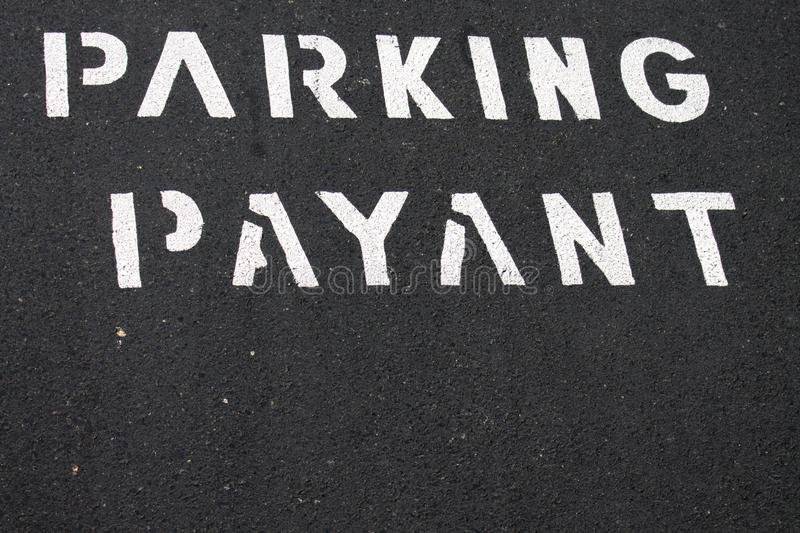 Text pay for parking in french. White text pay for parking in french on grey asphalt background stock photo