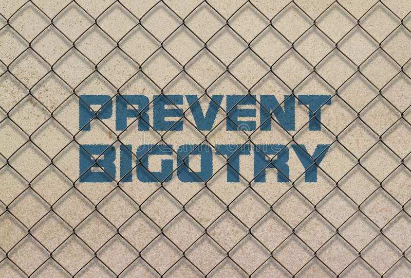Text Prevent Bigotry. Written in blue under a wire mesh royalty free stock photo