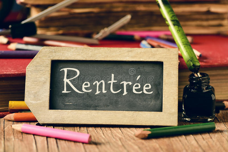 Text rentree, back to school in french. Label-shaped chalkboard with the text rentree, back to school in french, some old books and old stationery such as a pen royalty free stock image