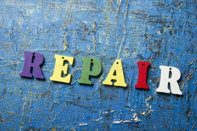 Text of REPAIR on colorful wooden abc letter at abstract grunge blue background stock photography