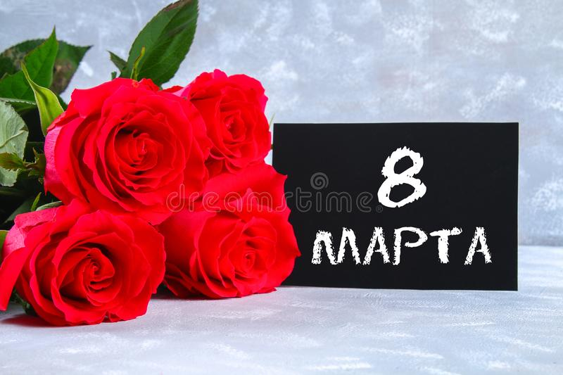 Text in Russian: March 8. Black chalkboard and roses. International Women`s Day. Text in Russian: March 8. Black chalkboard and roses. International Women`s Day stock photography