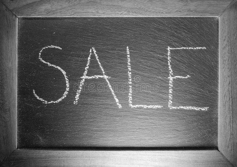 Text sale written on chalkboard in black and white stock images